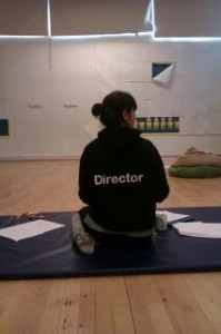 Director Gemma pictures from the back in black top that says 'director' on it.