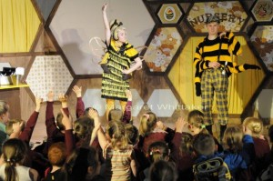 Sophie Bee in bee costume doing a disco pose hand pointing